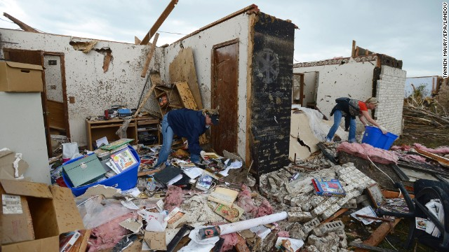 People recover belongings from the rubble of a home in Moore.