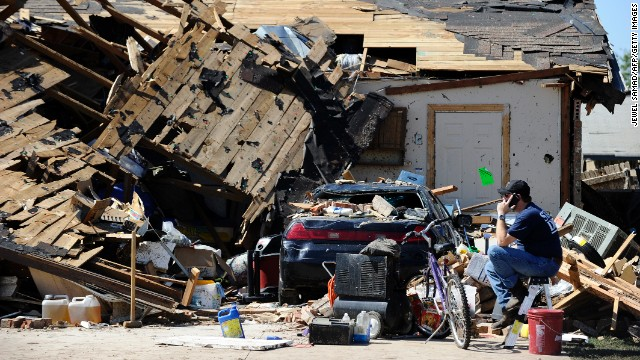 A man talks on his cell phone in front of a destroyed house on May 22.
