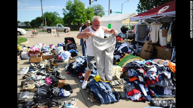 A man looks through a pile of clothing at a roadside relief camp on May 22 in Moore.
