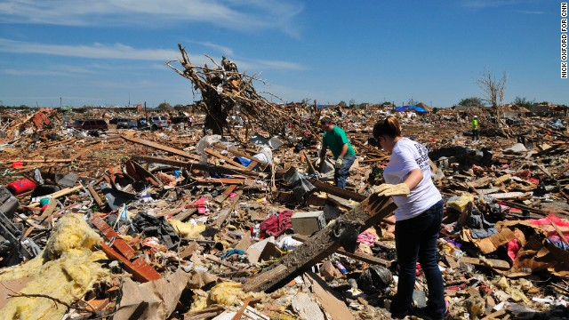 Jason Keen and his wife, Katy, search through the wreckage in a field of debris behind their house.