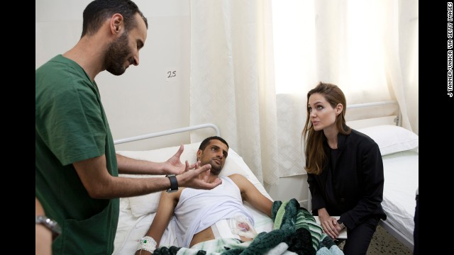 Jolie visits a man in a hospital in Misrata, Libya, on October 11, 2011, in this handout photo provided by UNHCR.