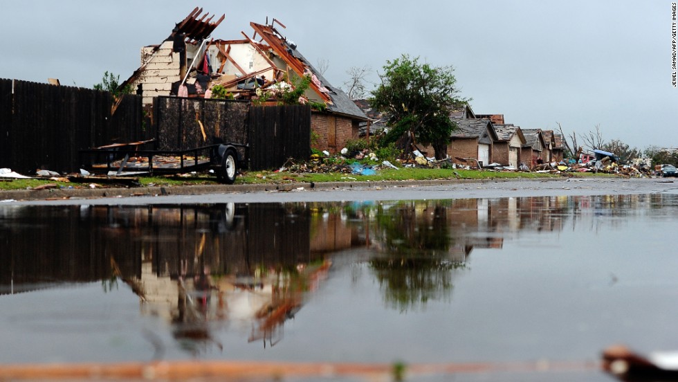 Rubble lines a wet street in a tornado-devastated neighborhood in Moore, Oklahoma, on Thursday, May 23. Severe thunderstorms barreled through this Oklahoma City suburb at dawn Thursday, complicating cleanup efforts three days after a powerful tornado ripped through the area. Click through to see other images of weather around the world.