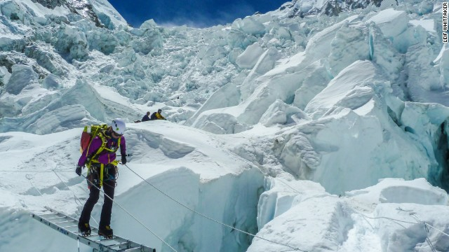 Expedition member Melissa Arnot uses a ladder to cross in the Khumbu Icefall in 2012.