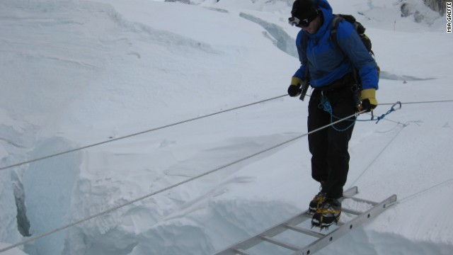 A photo shows Jon Kedrowski crossing a crevasse in the Khumbu Icefall on a ladder.