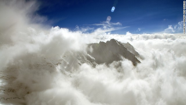 The peak of Nuptse, just over a mile southwest of Everest, is visible amongst the clouds in the Nepalese Himalayas.