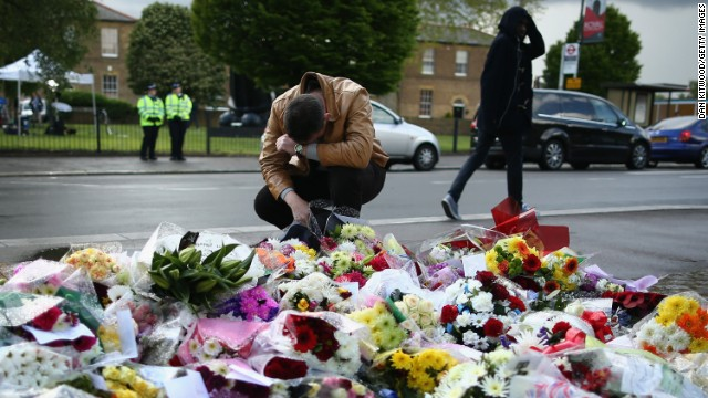 A man contemplates the scene where a British soldier was murdered in Woolwich, London; flowers have been laid in the street.