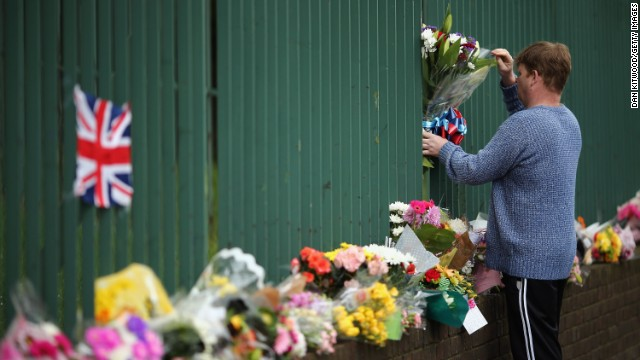 A man places flowers near the scene on May 24.