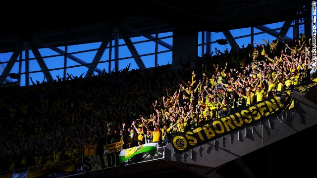 Borussia Dortmund fans in the upper deck of Wembley Stadium cheer for their team.