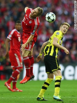 Bastian Schweinsteiger of Bayern performs a header against Marco Reus of Borussia Dortmund.