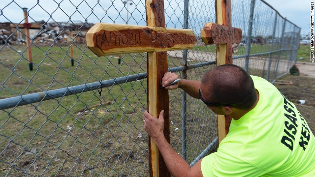 A volunteer signs a cross on May 25 at a makeshift memorial outside of the destroyed Plaza Towers Elementary School where seven children were killed in Monday's tornado in Moore.