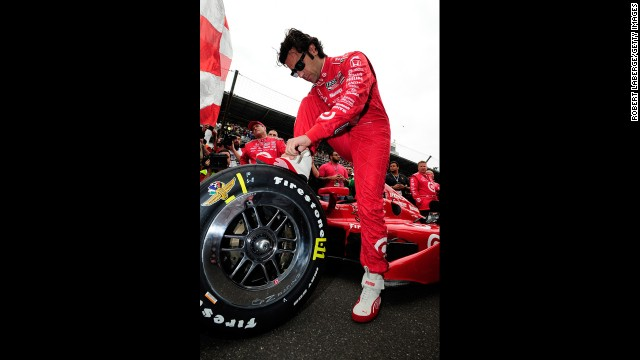 Dario Franchitti of Scotland makes adjustments to his car before the start.