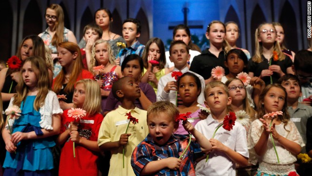 Preschooler Keltin Marazzi, front center, stands on stage with other school children during the memorial service.