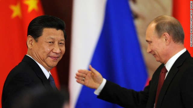 File photo of Russia's President Vladimir Putin greeting Chinese President Xi Jinping in March.