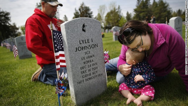 Desiree Neal visits the grave of her grandfather, Army Sgt. Lyle Johnson, with her daughter, Sophia, and her husband, Ryan, during a Memorial Day weekend service at the State Veterans Cemetery near Little Falls, Minnesota, on Sunday, May 26. Johnson was a Korean War veteran who died in 2011.