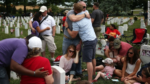 Friends and family gather at Arlington National Cemetery on May 27 to visit the grave site of Army Capt. Ronald George Luce Jr. He died in a roadside bombing in Afghanistan in 2009.