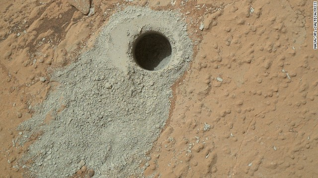 "Curiosity drilled into a rock target called ""Cumberland"" on May 19, 2013, and it collected a powdered sample of material from the rock's interior. The sample will be compared to an earlier drilling at the ""John Klein"" site, which has a similar appearance and is about 9 feet away."