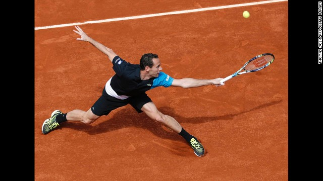 France's Michael Llodra hits a backhand shot to Canada's Milos Raonic on May 29. Raonic beat Llodra 7-5, 3-6, 7-6(3), 6-2.