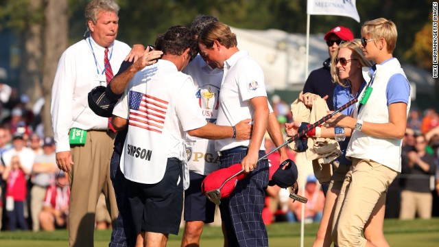 Bubba Watson, Webb Simpson and their caddies pray during the 39th Ryder Cup at Medinah, Illinois. They were later met by their wives, who also joined in the huddle.