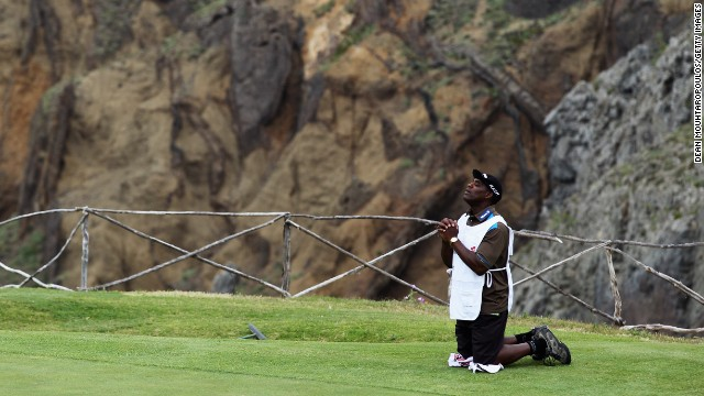 Hugo Benson, caddy of Finnish golfer Roope Kakko, kneels down on the 14th green and prays during the final round of the 2011 Madeira Islands Open.