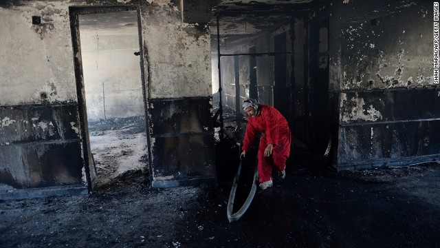 A firefighter inspects the interior of the provincial governor's office following a suicide attack in Bazarak, on May 29, 2013.