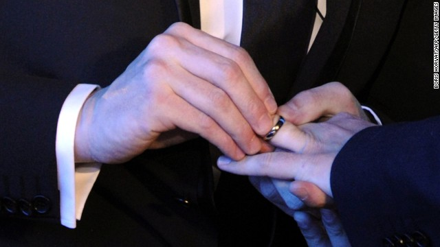 A same-sex couple exchange wedding rings at their marriage ceremony.