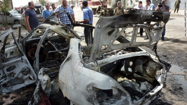 People inspect the site of a blast Thursday in Baghdad, one of many in the recent surge of violence in Iraq.