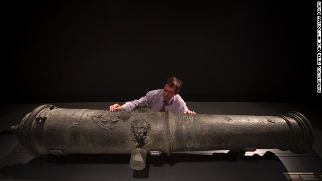 Maintenance Coordinator Brian Robinson poses next to a canon recovered from the wreck.