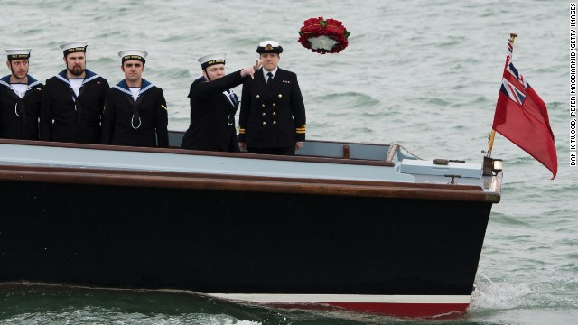 Able Seaman 1st Class Luke Checkley throws a wreath from the deck of WWII seaplane tender, commemorating those who died when the warship sank in 1545.