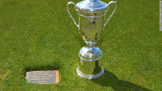 The U.S. Open trophy is paraded next to the plaque on the 18th hole which marks the point from which Hogan played his famous shot.