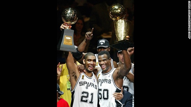 Duncan and David Robinson, aka the Twin Towers, hold up the MVP and championship trophies, respectively, after winning their second championship by toppling the New Jersey Nets in six games in the 2003 NBA Finals.