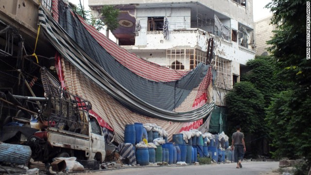 A man walks past a wall of barrels and linens on Wednesday, May 29, erected in Homs to provide protection from snipers.
