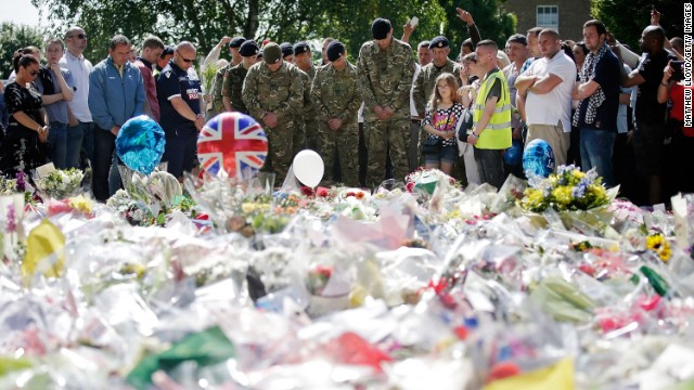 People and soldiers gather Sunday outside the Royal Artillery Barracks, near where British soldier Lee Rigby was killed May 22.