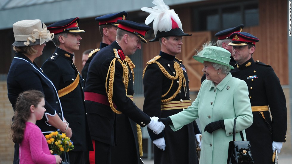 Britain's Queen Elizabeth II is greeted by officers on Friday, May 31, during a visit to the King's Troop Royal Horse Artillery at Woolwich Barracks in London. These barracks housed British soldier Lee Rigby, who worked as a military recruiter as well as a ceremonial drummer. Rigby was killed the week before, a couple of hundred yards from the Royal Artillery Barracks.