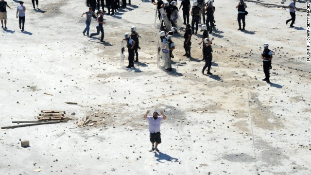 A man flees the clashes between Turkish protestors and riot police on June 1. On Friday, May 31, riot police stormed the growing camp in Gezi Park with water cannons and tear gas, pushing protesters into surrounding streets and triggering the clashes that have continued for more than 24 hours.