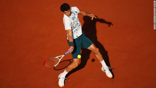 Dimitrov plays a forehand to Djokovic.