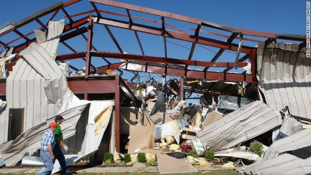 Two men walk by a damaged OKC-West Livestock Market building near El Reno on June 1.