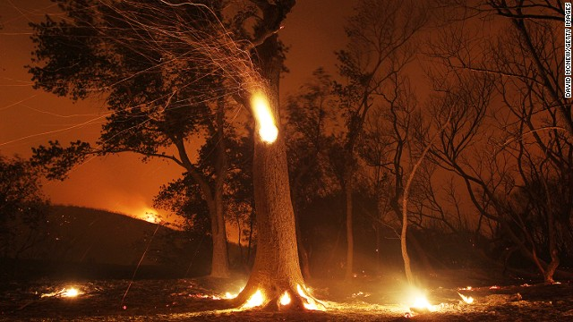 Sparks fly from a hollowed burning tree at the Powerhouse Fire on Sunday, June 2, near Lake Hughes, California.