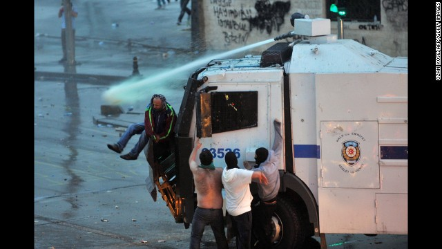 Protesters cling to a police vehicle mounted with a water canon in Istanbul on June 2.