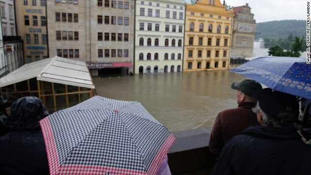 Onlookers watch the water rise around houses on the Vltava River in Prague. The Vltava was cresting Tuesday in the Czech capital, but areas downstream still faced rising waters.<!-- --> </br>