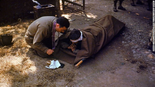 A U.S. Army chaplain kneels next to a wounded soldier to administer the eucharist and last rites, France, 1944.<br />