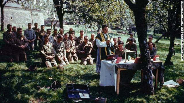 A church service is conducted in dappled sunlight, France, 1944.