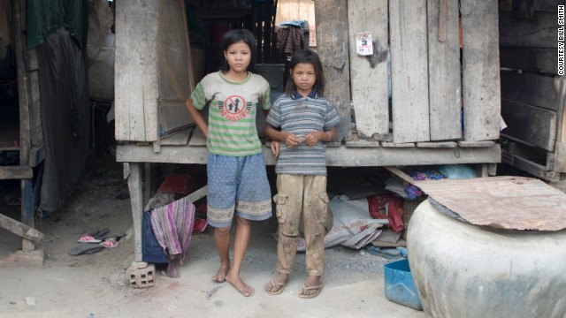 Sreyna, right, and her sister Salim stand in front of their house near the dump. They had no electricity or running water.