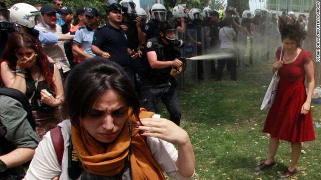 A riot police officer uses tear gas as people protest the destruction of a park for a pedestrian project in Istanbul, Turkey's Taksim Square on Tuesday, May 28, 2013. The woman in red has become the face of the protests.