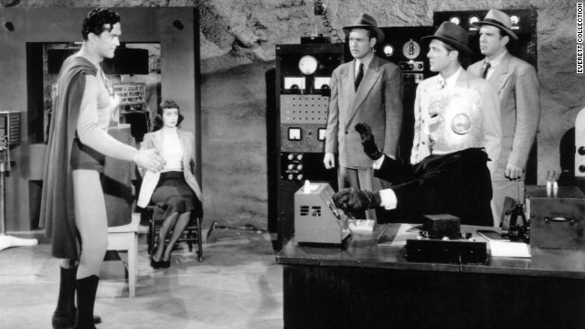 "Alyn revisits his role as Superman in the 1950 film serial ""Atom Man vs. Superman."" Lyle Talbot, seated at right, plays the supervillain Lex Luthor, the Atom Man."