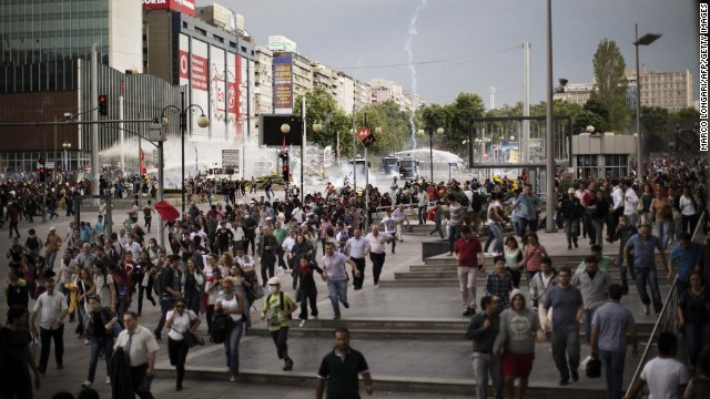Demonstrators run for cover as police use water cannons and tear gas on the crowd in Ankara on June 5.