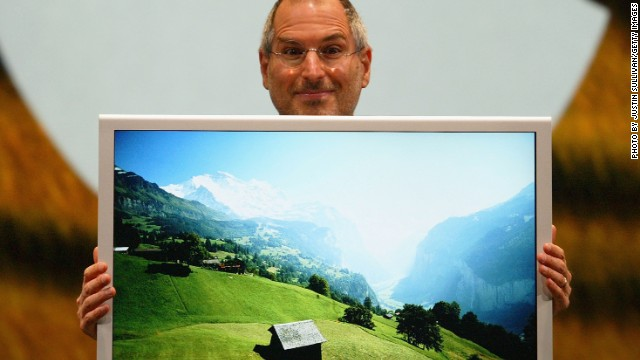 Jobs posed here with a new flat-panel display, the first 30-inch model designed for the personal computer. He also announced the 2005 release of OSX Tiger.
