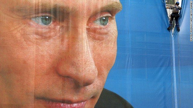 A worker takes down a giant elections poster bearing a portrait of Putin on October 13, 2009, in Moscow. Putin's party tightened its grip on Russian politics with a sweeping victory in local elections, officials said, as the opposition alleged widespread fraud.