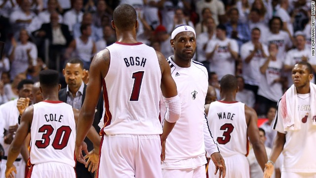 Miami Heat teammates walk off the court during a timeout in the second half.