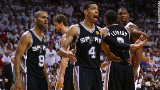 Members of the San Antonio Spurs react while taking on the Miami Heat.