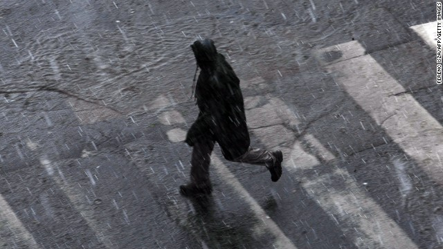 A man crosses a street as a storm hits downtown Budapest, Hungary, on Saturday, June 8.